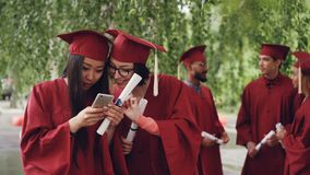 Female graduates are using smartphone looking at screen talking and laughing standing outdoors holding diplomas, girls. Female graduates are using smartphone stock video footage