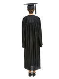 Female in graduation cap and gown standing back Royalty Free Stock Photo