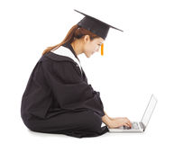 Female graduation sitting and  typing on a laptop Stock Photography