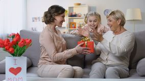 Female grandchild covering granny eyes presenting surprise gift, mothers day. Stock footage stock footage