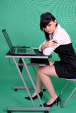 Female graphic designer with laptop and tablet pen. On green background Royalty Free Stock Images