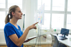 Female graphic designer looking at color chart while holding digital tablet. In office royalty free stock photo