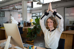 Female graphic designer performing yoga. In creative office Royalty Free Stock Image