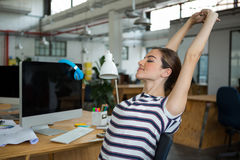 Female graphic designer sitting on chair and stretching her arms. In creative office Royalty Free Stock Photo