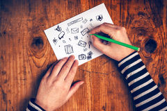 Female graphic designer sketching software icons on paper Stock Photography