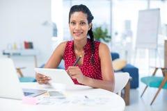 Female graphic designer using graphic tablet at desk stock image
