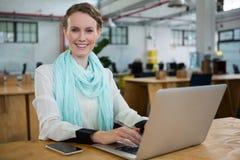 Female graphic designer using laptop at desk Stock Image
