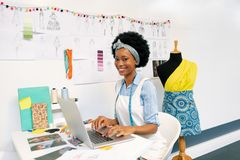 Female graphic designer using laptop in office royalty free stock photography