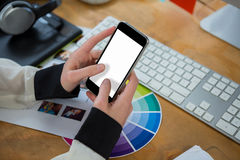 Female graphic designer using mobile phone at desk Royalty Free Stock Photos