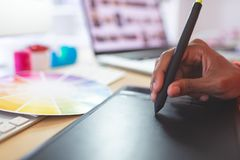 Female graphic designer using graphic tablet at desk. Close-up of young mixed-race female graphic designer using graphic tablet at desk stock photos