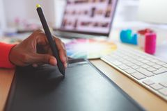 Female graphic designer using graphic tablet at desk. Close-up of young mixed-race female graphic designer using graphic tablet at desk in a modern office royalty free stock image