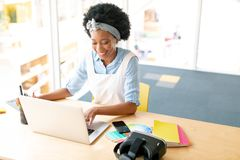 Female graphic designer using graphic tablet and laptop at desk. High angle view of African american female graphic designer using graphic tablet and laptop at stock photography
