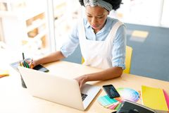 Female graphic designer using graphic tablet and laptop at desk stock image
