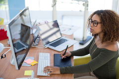 Female graphic designer working on computer while using graphic tablet at desk stock photo