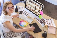 Female graphic designer working on graphic tablet at desk in office. Portrait of young Caucasian female graphic designer working on graphic tablet at desk in stock photo