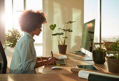 Female graphic designer working at her desk. Side view of female graphic designer working with digital drawing tablet and pen on a computer in office. African stock photography