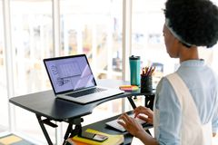 Female graphic designer working on laptop at desk. Side view of African american female graphic designer working on laptop at desk in office stock images