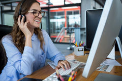 Female graphic designer working over computer at desk Royalty Free Stock Images