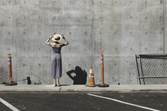 Female in Gray Dress Near Road Cone Staring at Wall Concrete Wall Stock Images