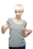 Female in gray t-shirt. Vertical studio portrait of young attractive short-cut blond brown-eyed caucasian teenage female dressed in light-gray t-shirt and blue Stock Photo
