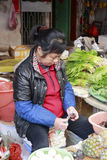 Female greengrocer peeling water chestnuts in the market Stock Image