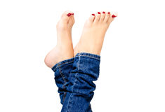 Female groomed feet in jeans Royalty Free Stock Images