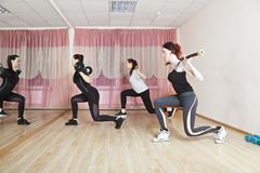 Lunge with rods. Female group exercises lunge with heavy rods. Horizontal shot Royalty Free Stock Images