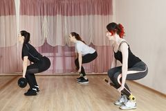 Sit-ups with sticks. Female group making sit-ups with heavy sticks. Horizontal shot Stock Images