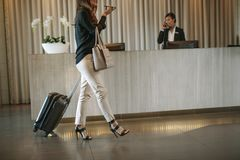 Female guest arriving in hotel with suitcase. Business women walking in front of hotel reception with luggage and having a phone call. Female guest arriving in Stock Images