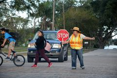 FEMALE GUIDING SCHOOL CHILDREN IN TRAFFIC. OCOEE/ORLANDO / FLORIDA / USA - 01 December _2017. _ Female directing traffic for school children in Ocoee, Photo royalty free stock images