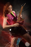 Female guitar player. Photo of a female guitarist playing on a stage. Shot with strobes and slow shutter speed to create lighting atmosphere and blur effects Royalty Free Stock Images