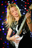 Female guitar player. Blond female guitar player on stage Royalty Free Stock Image