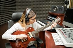 Female guitarist composing music in studio Stock Photo