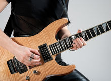 Female guitarist playing electric guitar. Female guitarist playing hard rock style electric guitar stock photography