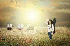 Female guitarist posing in automn grass field Stock Photo