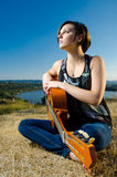 Female guitarist posing outdoors Royalty Free Stock Photo