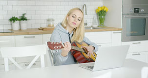 Female guitarist practicing at home Royalty Free Stock Image