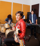 Female Guitarist Singing While Performing With Band Stock Images