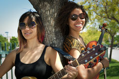 Female guitarist and violinist smiling outdoors Stock Photography