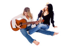 Female guitarists tuning their guitars Royalty Free Stock Image