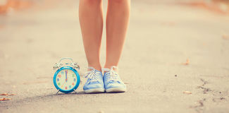 Female gumshoes. Teenager's foots and alarm clock in gumshoes in the park Stock Image