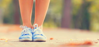 Female gumshoes. Teenager's foots in gumshoes in the park Stock Image