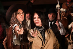 Female Gun Fighters. Serious ladies in western wear draw their revolvers Stock Photography