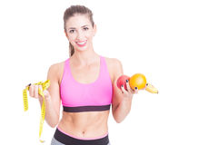 Female at gym holding tape line and fruits Stock Photo