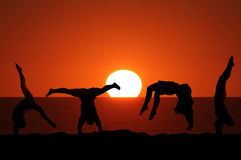 Female gymnast on beach in sunset. Silhouette of female gymnast on beach in sunset doing handstand etc royalty free stock photography
