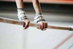 Female gymnast. Hands grips athletes female gymnast exercises on uneven bars royalty free stock images