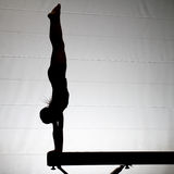 Female gymnast handstand. Young female gymnast doing a handstand on balance beam royalty free stock photos