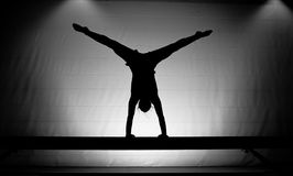 Female gymnast handstand. Young female gymnast doing a handstand on balance beam stock photography