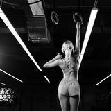 Female gymnast hanging on gymnastic rings. Slim beautiful female gymnast with long blonde braid, dressed in pink crop top, shorts and white trainers, hanging on Royalty Free Stock Photos