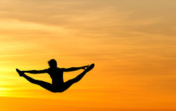 Female gymnast jumping in sunset Stock Image